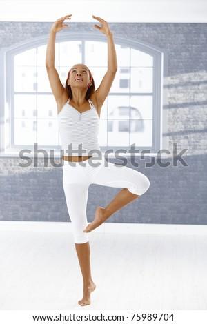 Pretty ballet dancer girl in ballet pose in classroom, raising arms.? - stock photo
