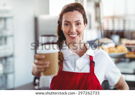 Pretty barista giving take-away cup at the cafe - stock photo