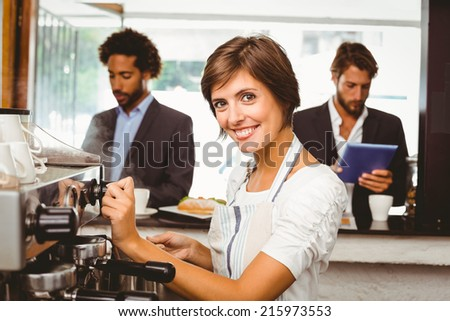 Pretty barista making cup of coffee at the coffee shop - stock photo