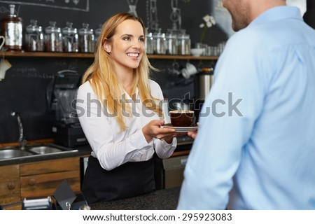 Pretty barista offering cup of coffee to restaurant client - stock photo