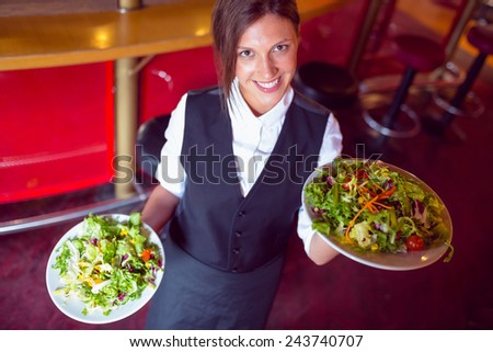 Pretty barmaid holding plates of salads in a bar - stock photo