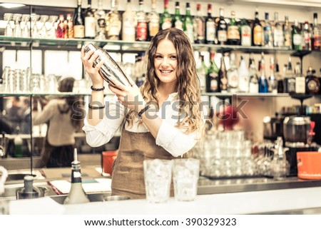 Pretty barmaid shaking cocktails in a bar - Female bartender preparing drinks for guests - stock photo