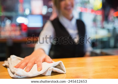 Pretty barmaid wiping down bar in a bar - stock photo