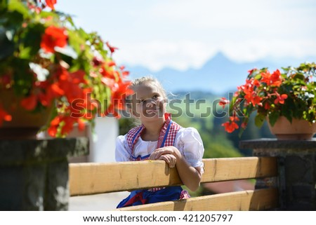 Pretty bavarian girl with flowers on the farm . Alps in background. Germany. - stock photo