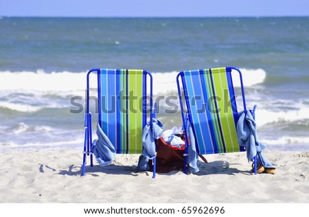 pretty beach scene with two chairs sitting in surf - stock photo