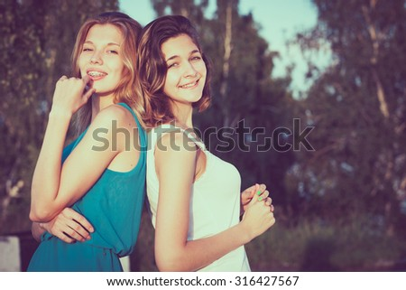 Pretty beautiful brunette and blonde girl friends having fun. Both standing in park and smiling (laughing). Concept of female friendship. - stock photo