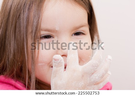 Pretty beautiful girl covered in flour makes cakes. - stock photo