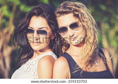 Pretty beautiful girl friends in sunglasses having fun. Both looking at camera and smiling (laughing). Concept of female friendship. - stock photo