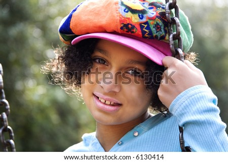 pretty biracial girl sitting on swing...backlit by the sun - stock photo