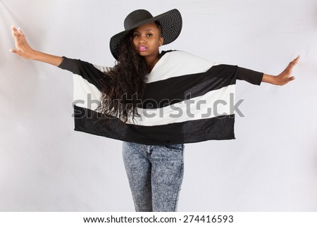 Pretty black woman in a hat and black and white blouse,looking thoughtfully at the camera and spinning around with arms out - stock photo