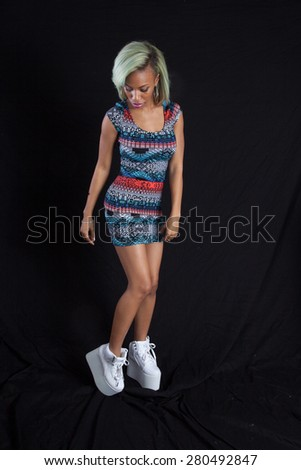 Pretty black woman in colorful dress, standing on her toes - stock photo
