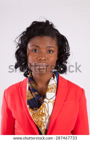 Pretty black woman in red jacket with a thoughtful expression - stock photo