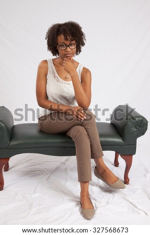 Pretty black woman with glasses looking thoughtfully at the camera with her chin on her hand - stock photo