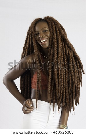 Pretty black woman with long dreadlocks looking  at the camera with a happy smile - stock photo