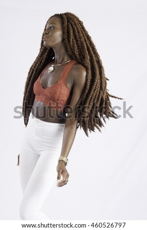 Pretty black woman with long dreadlocks looking thoughtful - stock photo
