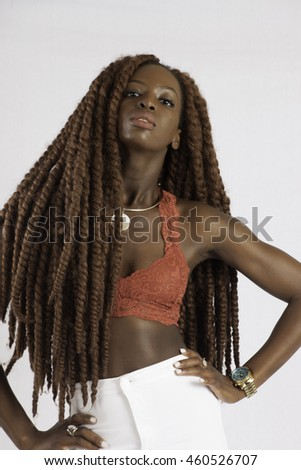 Pretty black woman with long dreadlocks looking thoughtfully at the camera - stock photo