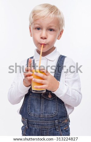 Pretty blond boy is drinking orange juice through a straw with enjoyment. He is standing and holding a glass. The boy is looking at the camera happily. Isolated  - stock photo