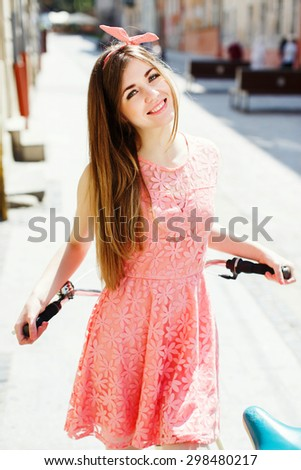 Pretty blond-brown girl with long hair, smiling and  holding a bicycle handlebar in a sunny day on the street of the old town. Wearing pink head wrap and pink dress with a pattern of flowers. - stock photo