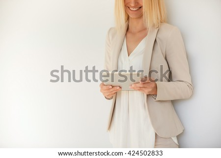 Pretty blond businesswoman in formal suit communicating with her partners via digital tablet computer standing against white studio wall background with copy spcae for your text or advertising content - stock photo