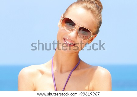 Pretty blond female with sunglasses on at the beach - stock photo