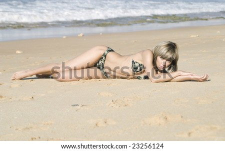 Pretty blond girl laying on the sand next to see - stock photo
