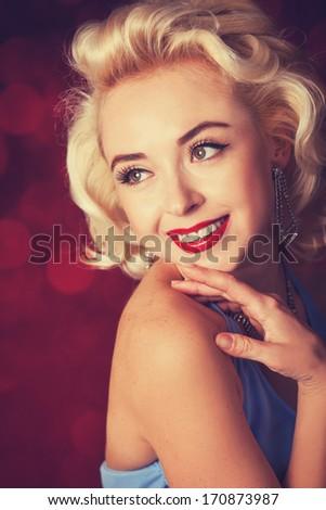 Pretty blond girl model like Marilyn Monroe on red background - stock photo