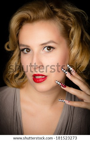 Pretty blond girl model like Marilyn Monroe with sensual red lips and long nails isolated on black background - stock photo
