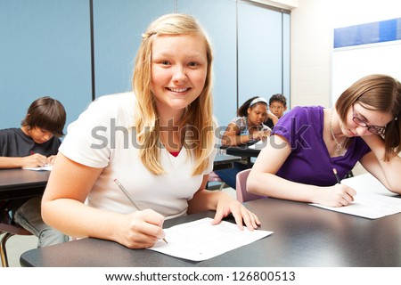 Pretty blond girl sitting in her high school class. - stock photo