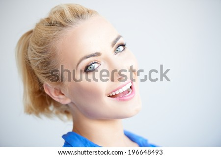 Pretty blond girl standing sideways turning and laughing at the camera  head and shoulders on grey - stock photo