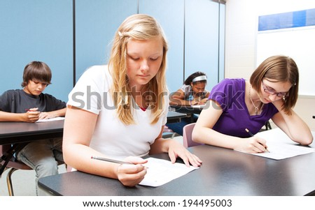 Pretty blond girl taking a test with her high school class.   - stock photo
