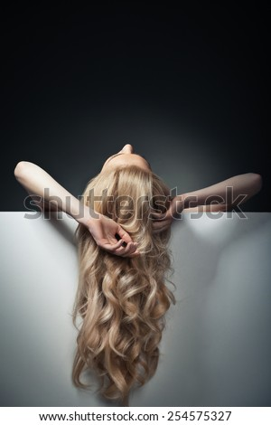 pretty blond model hiding behind a big blank sheet of paper and looking up her hands haging freely. - stock photo