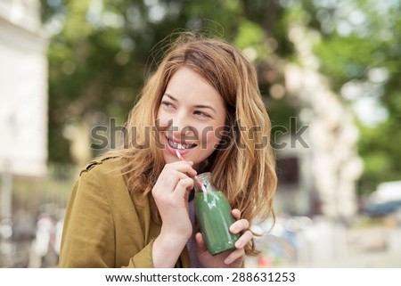 Pretty Blond Teen Girl Drinking a Bottle of Green Juice with Straw While Smiling Into Distance. - stock photo