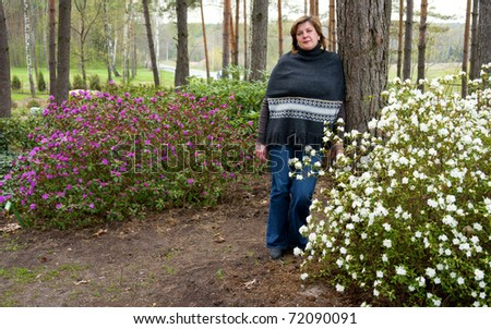 Pretty blond woman among the flowering shrubs of rhododendrons - stock photo