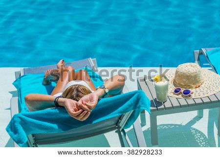 Pretty blond woman  enjoying a fresh cocktail in a swimming pool - stock photo