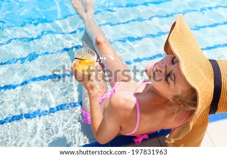Pretty blond woman in a hat enjoying cocktail in a swimming pool - stock photo