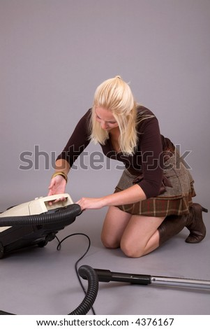 Pretty blond woman trying to fix the broken vacuum cleaner - stock photo