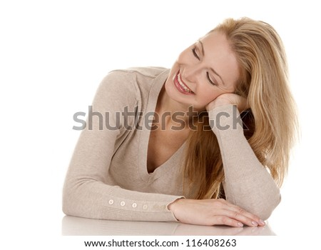 pretty blond woman wearing beige top sitting on white background - stock photo