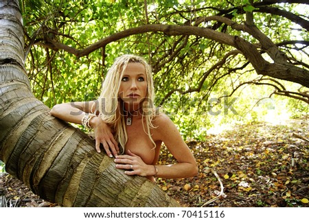 Pretty Blond woman with braids nude in the forest - stock photo
