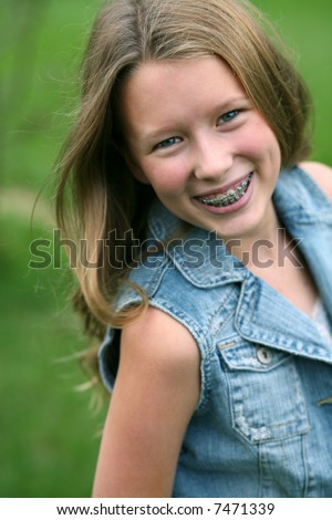 pretty blond young teen girl smiling with braces - stock photo