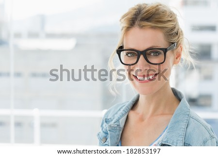 Pretty blonde designer smiling at camera in creative office - stock photo