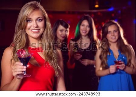 Pretty blonde drinking a cocktail at the nightclub - stock photo