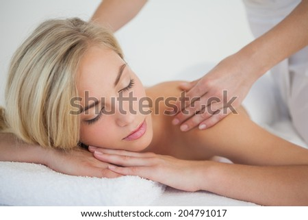 Pretty blonde enjoying a massage at the health spa - stock photo