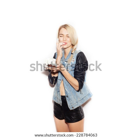 Pretty blonde girl eating chocolate Cake. Indoor lifestyle portrait of woman in sunglasses.  White background, not isolated - stock photo