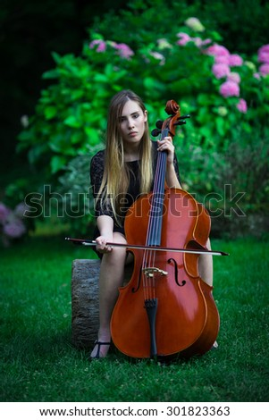 Pretty blonde girl in black dress playing a cello in a rural outdoor - stock photo