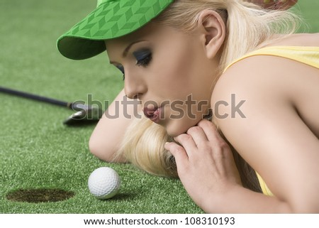 pretty blonde girl is lying on the grass and playing with golf ball, she is in profile, looks the ball and blows on that - stock photo