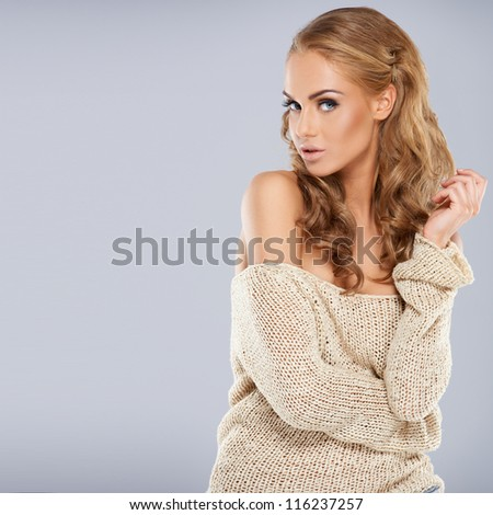 Pretty blonde girl posing while isolated against a grey background - stock photo