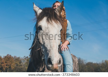 Pretty blonde girl riding her grey horse in the countryside - stock photo