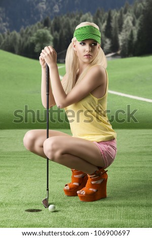 pretty blonde girl's playng golf with golf club, pink shorts and green sunshade, she is turned of three quarters at right, folded down with golf club between her legs - stock photo
