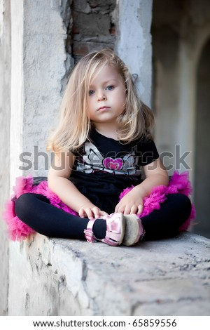 Pretty blonde girl sitting on ruins - stock photo
