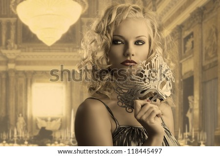 pretty blonde girl with curly hair takes one silver mask, she is turned of three quarters at left, looks at right and takes the mask with right hand - stock photo